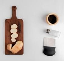 Pommes de terre coupées et tranchées sur une planche à découper avec sel poivre noir et coupe-croustilles sur fond blanc