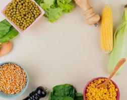 Vue de dessus des bols de graines de maïs séchées et cuites pois verts épinards laitue épis de maïs sur fond blanc avec copie espace photo
