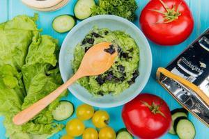Vue de dessus de la salade de légumes avec laitue concombre tomate coriandre et râpe avec cuillère en bois sur fond bleu photo