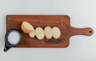 Vue de dessus de la pomme de terre coupée et tranchée et sel sur une planche à découper sur fond blanc