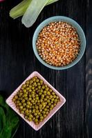Vue de dessus des bols avec des graines de maïs séchées et des pois verts sur fond noir photo