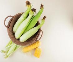 Vue de dessus du panier avec cors non cuits et coquille de maïs avec cors cuits sur le côté droit et fond blanc avec copie espace