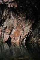 Formation rocheuse brune et grise à côté du plan d'eau pendant la journée photo