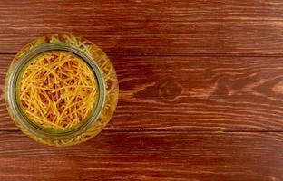 Vue de dessus des pâtes spaghetti dans un bol sur fond de bois avec espace copie photo