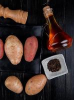 Vue de dessus des pommes de terre dans la plaque avec des graines de poivre noir beurre fondu sel sur fond de bois photo