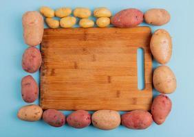 Vue de dessus des pommes de terre autour d'une planche à découper sur fond bleu photo
