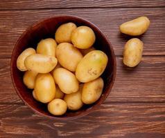 Vue de dessus des pommes de terre dans un bol sur fond de bois photo