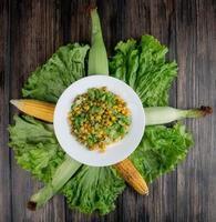 Vue de dessus de la salade de maïs avec de la laitue et des pois verts avec des cors sur fond de bois photo