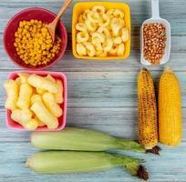 Vue de dessus des épis de maïs avec des céréales pop de maïs et des graines de maïs sur fond de bois