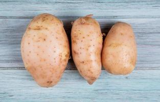Vue de dessus des pommes de terre rousses sur fond de bois photo