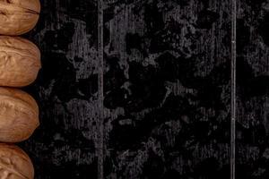 Vue de dessus de noix entières bordées dans une rangée sur fond de bois noir avec copie espace photo