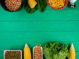 Vue de dessus des cors et des graines de maïs avec des pois verts épinards laitue salée sur fond vert avec copie espace