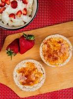 Vue de dessus des pains croustillants croustillants enduits de confiture et de fraises sur une planche à découper avec de l'avoine sur fond rouge et blanc