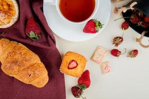 Vue de dessus du croissant de pain croustillant croquant sur tissu et tasse de thé aux fraises et cupcake au chocolat blanc sur fond blanc