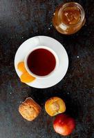Vue de dessus de la tasse de thé aux raisins secs sur le sachet de thé et les pêches cupcake confiture de pêches sur fond noir et marron
