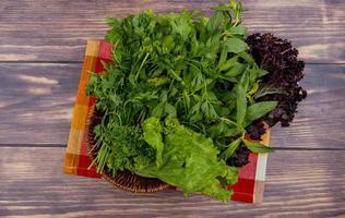 Vue de dessus des légumes verts comme la coriandre menthe laitue basilic dans le panier sur tissu sur fond de bois photo