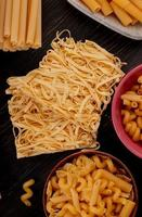 Vue de dessus des macaronis comme tagliatelle bucatini fusilli et autres sur fond de bois photo