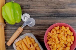 Vue de dessus des macaronis comme ziti et pipe-rigate dans des bols avec du poivre sur fond de bois