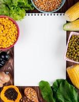 Vue de dessus du bloc-notes avec des graines de maïs laitue épinards graines de poivre noir pois verts avec copie espace