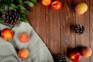Vue de dessus des pêches et des pommes de pin sur tissu sur fond de bois