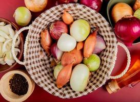 Vue de dessus des oignons dans le panier avec un en tranches dans un bol, beurre, graines de poivre noir sur fond rouge