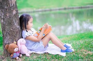 jolie petite fille lisant un livre avec une poupée dans le parc photo