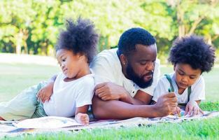 famille heureuse de s'allonger sur la pelouse dans le parc en vacances. concept d'amour et de liens familiaux photo