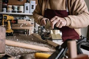 menuisier travaillant le bois avec une brosse électrique