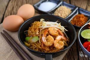 Pad thai crevettes dans une poêle noire avec des œufs et assaisonnement