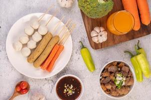 boulettes et brochettes de porc avec saucisses et légumes