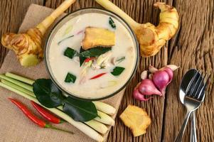 Tom kha kai, soupe de noix de coco thaï sur planche de cuisine en bois