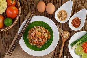 Pad thai crevettes dans un bol avec œufs, oignon nouveau et assaisonnements