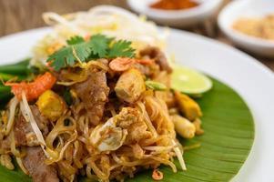 Pad thaï au citron, oeufs et assaisonnement sur une table en bois