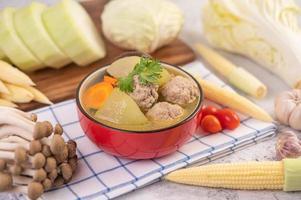 soupe aux boulettes de porc entourée d'ingrédients photo