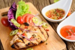 Poulet grillé sur une planche à découper en bois avec salade