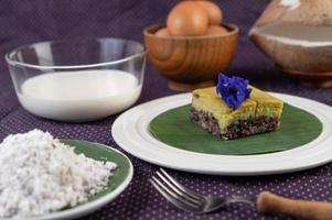 Riz gluant noir sur une feuille de bananier dans une assiette blanche avec des fleurs de pois papillon