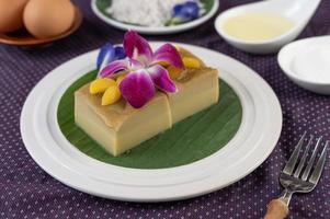 crème anglaise sur feuille de bananier avec fleurs de pois et orchidées photo