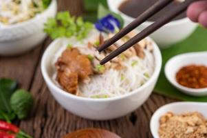 Nouilles au poulet dans un bol avec accompagnements thaïlandais