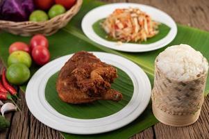 cuisses de poulet frites sur des feuilles de bananier avec riz gluant