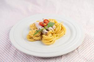 spaghetti et porc plaqués disposés sur une assiette blanche