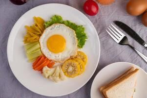 petit-déjeuner aux œufs frits avec œuf, salade, citrouille, concombre, carotte et maïs