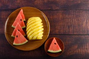 Tranches de pastèque et d'ananas sur une table en bois sombre