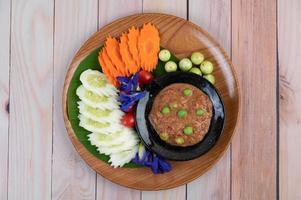 pâte de pâte de piment dans un bol avec aubergines, carottes, chili et concombres dans un panier