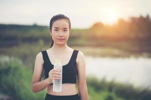 Young fitness teen holding bouteille d'eau après l'exécution de l'exercice photo