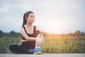 coureur de fitness adolescent se détendre avec de l'eau après l'entraînement photo