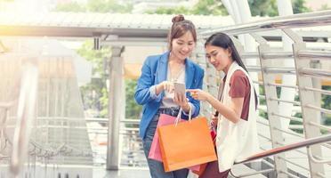 belles filles avec des sacs à provisions marchant au centre commercial