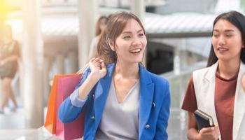 belles filles avec des sacs à provisions marchant au centre commercial photo