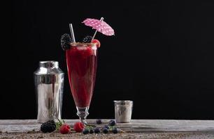 Cocktail de fruits des bois dans un verre sur un socle en bois décoré de mûres et d'un shaker