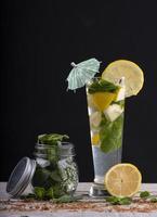 cocktail de jus de citron avec glace et menthe, accompagné d'un bocal en verre à la menthe sur un socle en bois.