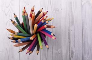 Crayons de couleur en bois, dans un bécher en cuir marron, vu de dessus, avec fond en bois blanc et gris